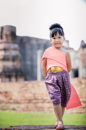 cute little girl: Cute little girl wearing typical thai dress on temple background