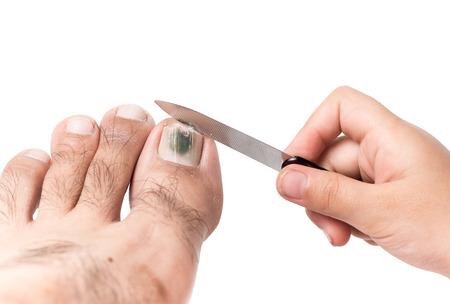 girl care: little hand use a nail file to clean toenail isolated