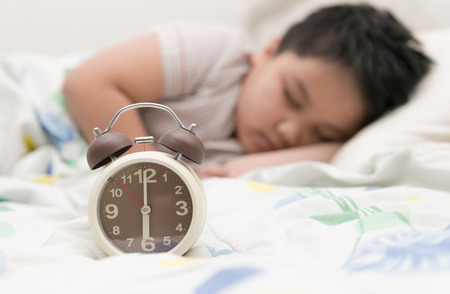 early morning: alarm clock and fat boy sleep on background Stock Photo