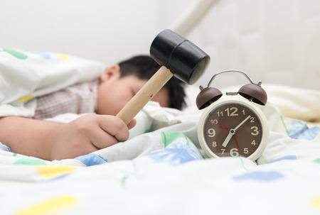 despertar: gordo trata de romper el despertador con el martillo en la mañana Foto de archivo