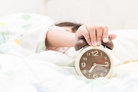 朝に目覚まし時計を差し伸べる手女の子