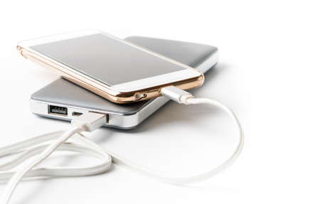 Smartphone charging with power bank on white background