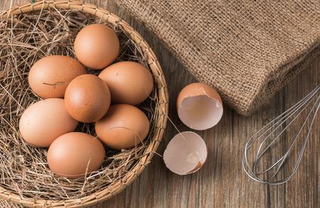 sackcloth: fresh egg in basket on wood background