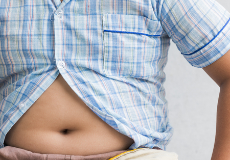 fat boy overweight. Tight shirt on gray background