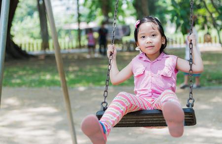swing seat: cute girl play swing seat in park Stock Photo