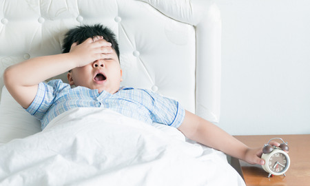 the yawn: fat boy yawn on bed in morning Stock Photo