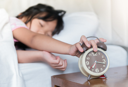 reaching out: Hand girl reaching out for alarm clock on morning