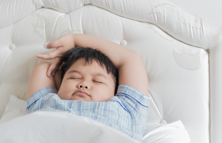 obesidad infantil: Sueño del muchacho de la grasa en la cama blanca Foto de archivo