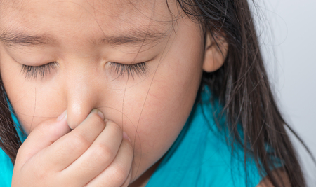 hyperhidrosis: close up of a girl holding her nose because of a bad smell on gray background