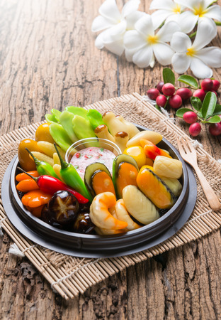 jelly beans: deletable imitation fruits or Kanom look choup (Thai Dessert) design to Seafood and vegetable on wood background.