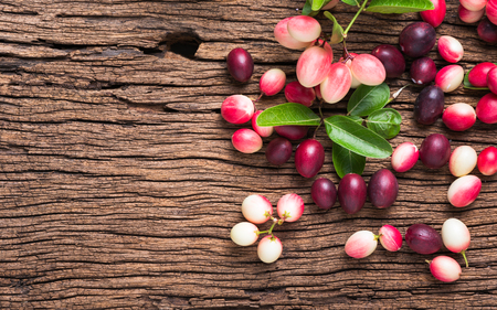 relieve: carunda fruit on old wood background, Fruit helps relieve sore throat and pituitary.