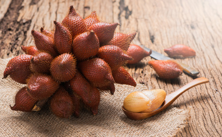 fresh Salak or Salacca fruit on wood spoon and old wood background
