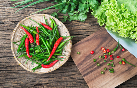 Thai chili on bamboo basket, and slice chilli on wood plate with vegetable. Foto de archivo