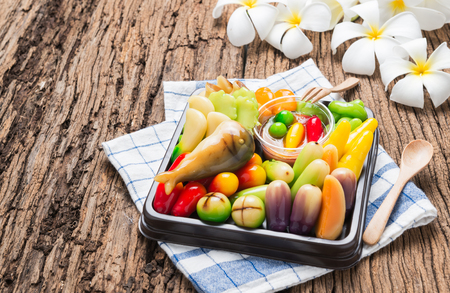 jelly beans: deletable imitation fruits or Kanom look choup (Thai Dessert) design to Fried mackerel with shrimp paste sauce and vegetable on wood background.