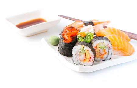 白い背景に、伝統的な日本料理に分離された白い皿にミックス寿司。
