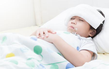 病気の子供の女の子がベッドと口の中に温度計で横になっています。