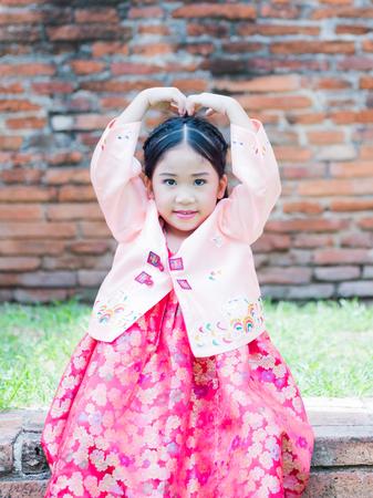 hanbok: cute girl wearing Korea costumes show love symbol hand in park