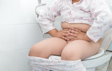 Fat boy sitting on the toilet. He is suffering of a diarrhea or stomachache.. Archivio Fotografico