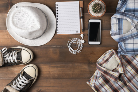 mobilephone: Travel preparations on wooden table, hat wallet, mobile-phone, notebook and shirt.