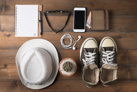 mobilephone: Travel preparations on wooden table, hat wallet mobile-phone notebook.