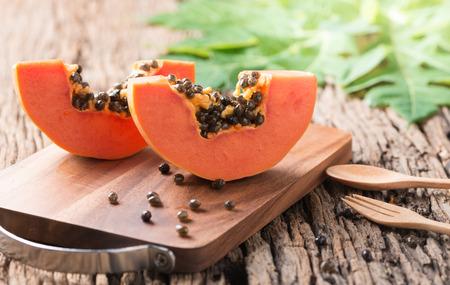 나무 블록 및 오래 된 나무 배경에 파파야 신선한 과일을 썰어 스톡 콘텐츠