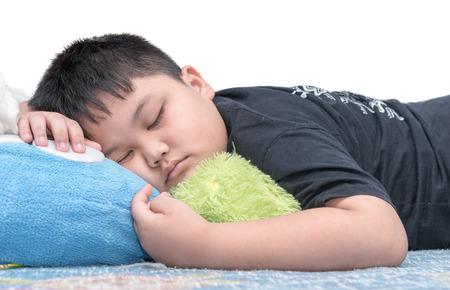 obesidad infantil: Sueño del muchacho de la grasa aislado en el fondo blanco.