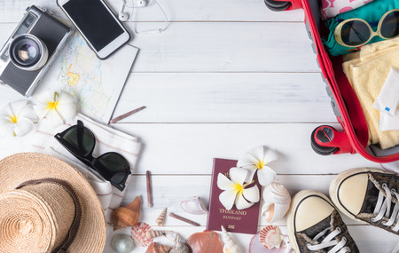 Summer holiday concept, prepare accessories and travel items vintage camera, smart phone, passport, sunglasses, sneaker and bag on white wooden board, flat lay, top view background.. Foto de archivo