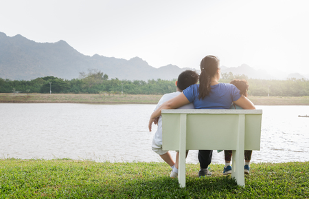 single mom: single Mom sit on chair with her son and daughter in park on morning.. Stock Photo