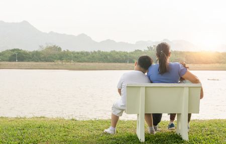 single mom: single Mom sit on chair with her son and daughter in park on morning