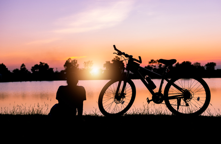 reflect: Silhouette woman sit near bicycle on sunset and lake background.. Stock Photo
