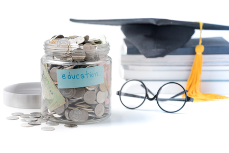 education budget concept. education money savings in a glass jar with glasses, graduate hat and book isolated on white background.