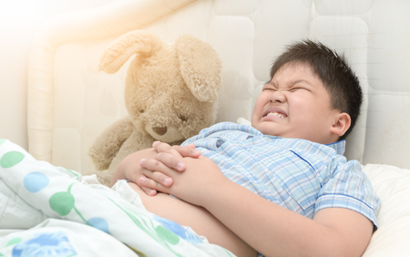 obese fat boy in him bed has a stomachache, healthy concept. Archivio Fotografico