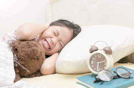 awakened: Annoyed girl being awakened by an alarm clock in her bedroom on morning. Stock Photo