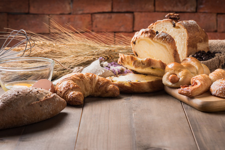 Assortment of baked bread and wheat on wood table background, homemade bakery.
