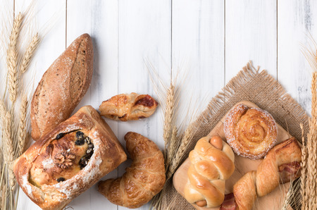 Assortment of baked bread and wheat on white wood background, homemade bakery. Stock Photo