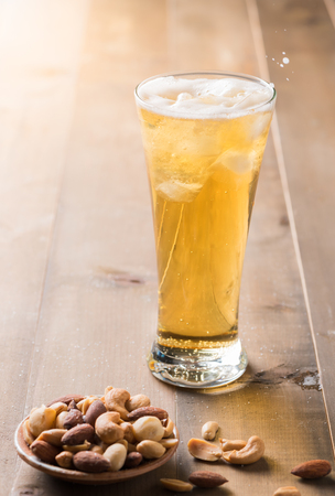 Cold beer with cocktail nut on wood background. Stock Photo