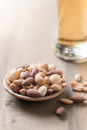 Salted mix cocktail nuts with beer and barley flower on wood background.