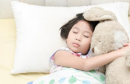 かわいいアジア女の子睡眠し、寝室のベッドにテディベアを抱擁 写真素材 - 72335209