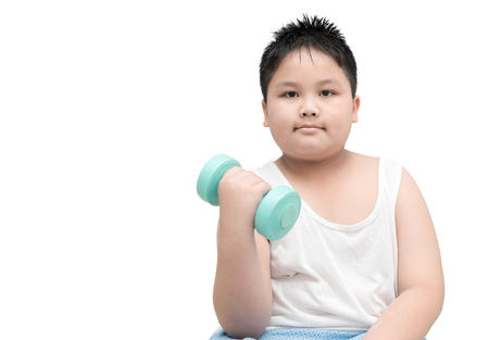 childhood obesity: obese fat boy is doing exercises with dumbbells; isolated on white background with copy space