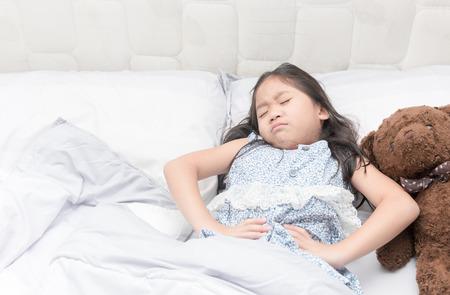 彼女のベッドで少女が腹痛、健康的な概念。