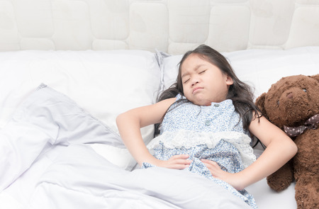 a little girl in her bed has a stomachache, healthy concept. Stockfoto