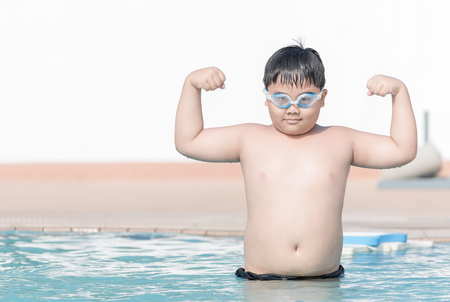 childhood obesity: obese fat boy show muscle in swimming pool, concept healthy and exercise.