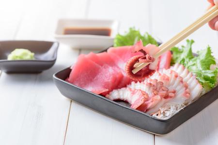 tuna fillet: fresh squid on chopstick and tuna sashimi on white wood background, Japanese food.