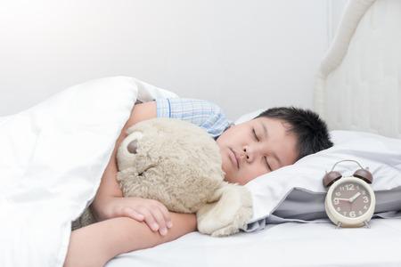 obesidad infantil: Sueño del niño obeso grasa y abrazo de oso de peluche en la cama, el concepto de salud. Foto de archivo
