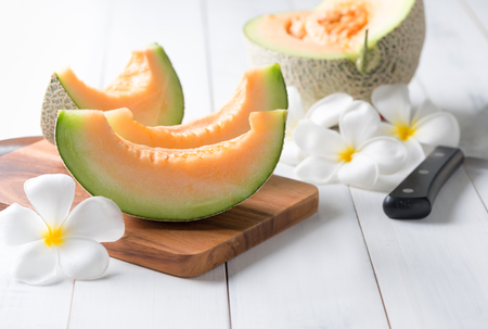Fresh sweet orange melon on white wooden table. Imagens