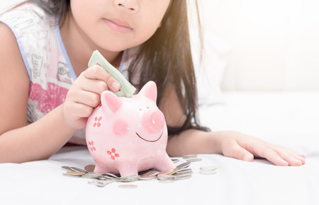 girl hand put money to piggybank on bedroom, concept saving for education