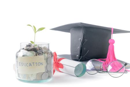 教育予算の概念。メガネ、大学院の帽子、白い背景で隔離の本のガラス瓶に教育のお金の節約と苗。