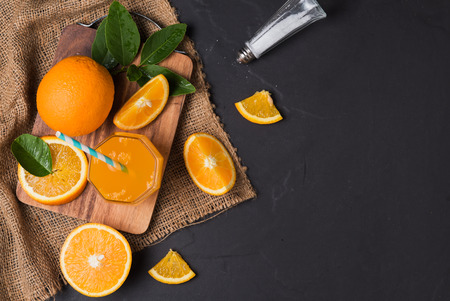 sweet segments: Fresh sliced orange and orange juice on black stone background, top view with copy space.