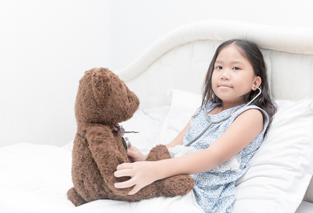 cute girl plays in doctor toy teddy bear and stethoscope.