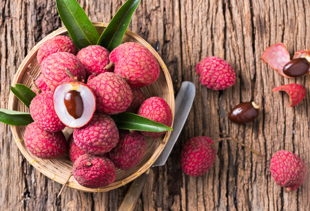 fresh organic lychee fruit on bamboo basket and old wood background.